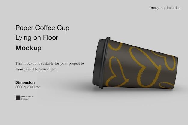 Бумажный кофейный стаканчик, лежащий на полу, макет
