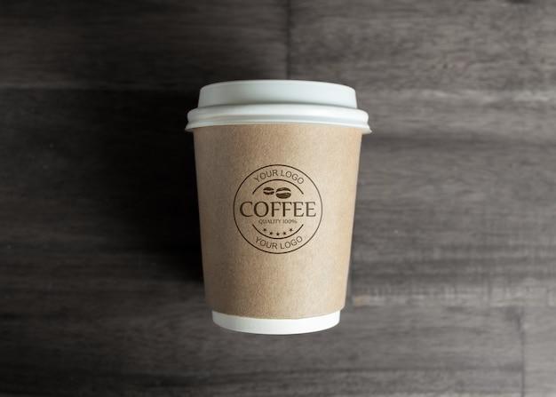 木製のテーブルの上の紙のコーヒーカップのモックアップ