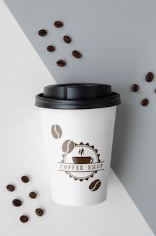 二色の背景に紙のコーヒーカップ