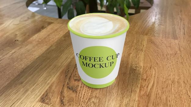 Бумажный кофейный стаканчик на макете столика в кафе