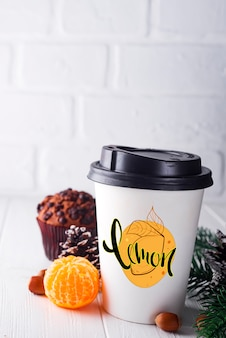 Paper cup of coffee surrounded by christmas decorations