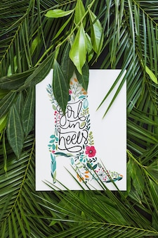 Paper mockup within tropical leaves