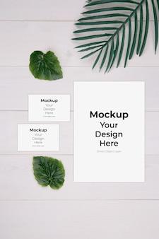 종이 시트 및 이름 카드 모형 및 나무 테이블에 잎