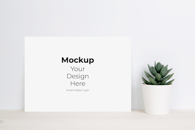 Paper sheet with mockup and plants in pot on wooden table