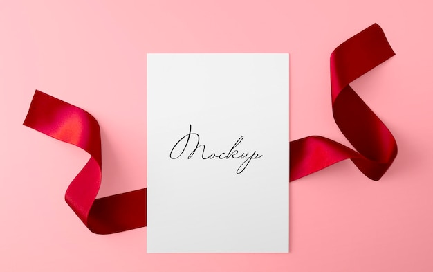 Paper sheet with red ribbon over pink surface mockup