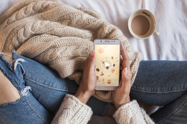 Person on bed looking at smartphone with autumn concept