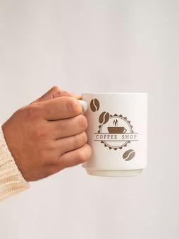 Лицо, занимающее макет чашку кофе