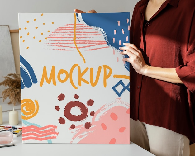 Person holding a canvas mock-up