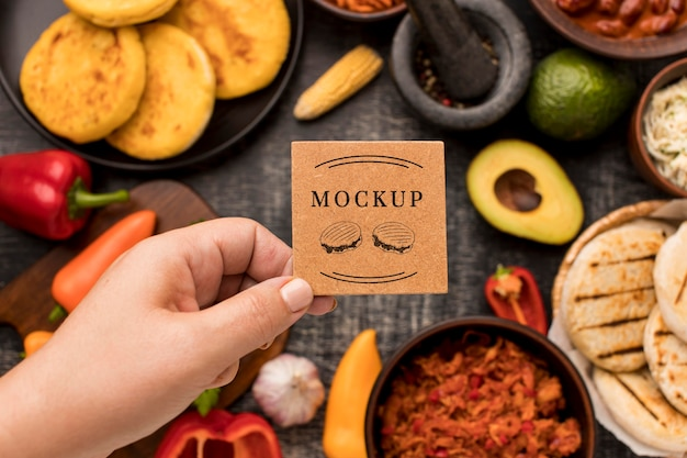 Person holding card with food mock-up
