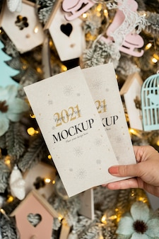 Person holding new year mock-up cards in front of christmas decorations