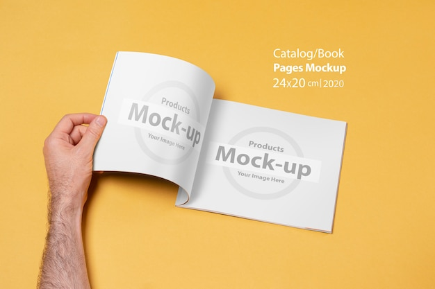 Person's hand opens a catalog
