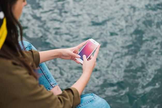 海の背景にスマートフォンモックアップを使用している人