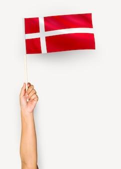 Человек размахивает флагом королевства дания