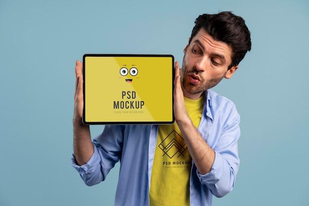 Человек с любопытным выражением лица в футболке и макете устройства
