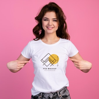 Person with excited expression pointing to tshirt mockup
