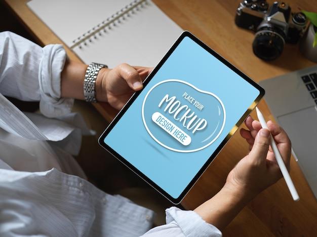 Человек, работающий с макетом цифрового планшета на рабочем столе в офисе