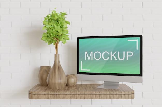 木製の壁のテーブルのパソコン画面のモックアップ