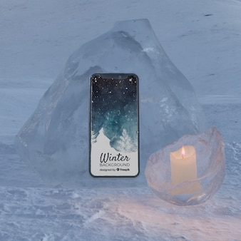 Phone on ice block light by candle