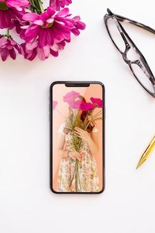 花とメガネの近くの電話のモックアップ