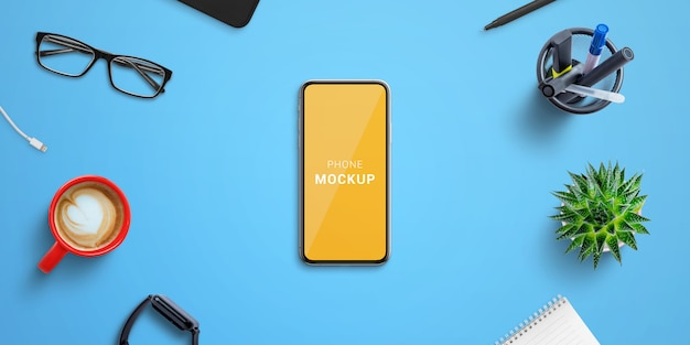 Phone mockup on blue office desk surrounded by office supplies. isolated screen for mockup, web site or app presentation. top vie, flat lay