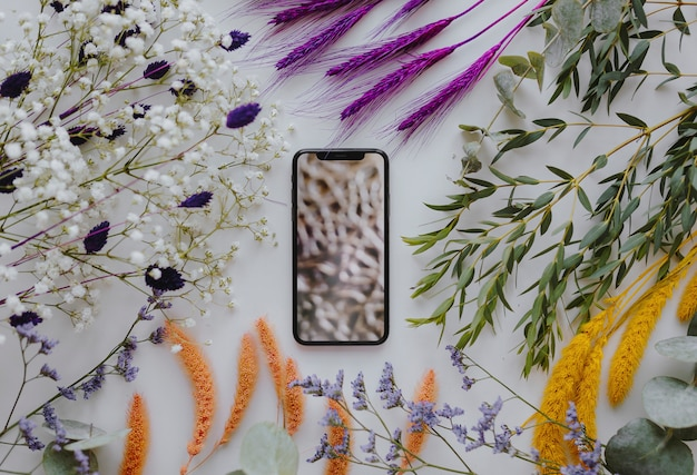 Phone mockup framed with a bunch of dried colorful flowers