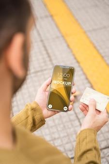 신용 카드를 가진 현대인이 들고 있는 전화 모형