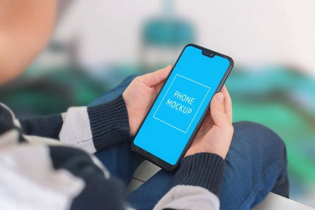 子供の手の中の電話のモックアップ。縁が薄い現代のスマートフォン。