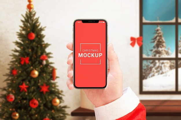 Phone mockup in santa claus hand with christmas decorations