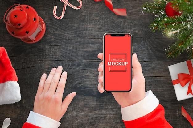 Phone mockup in santa claus hands flat lay