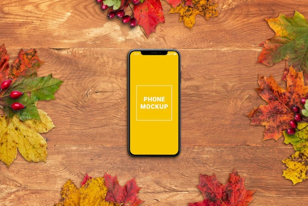 Phone mockup on wooden table surrounded by autumn leaves