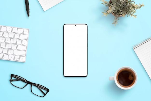 사무 용품으로 둘러싸인 파란색 작업 책상에 전화. 앱 또는 웹 페이지 반응 형 디자인 프로모션을위한 깨끗하고 평평한 구성