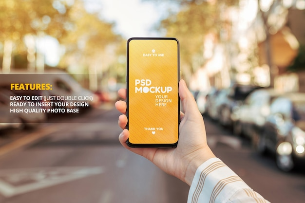 Phone screen mockup held by a woman's hand on the street