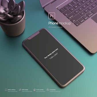 Phone setting next to a laptop at an abstract desktop mockup