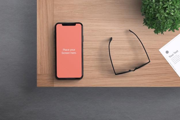 Phone with glasses on desk mockup