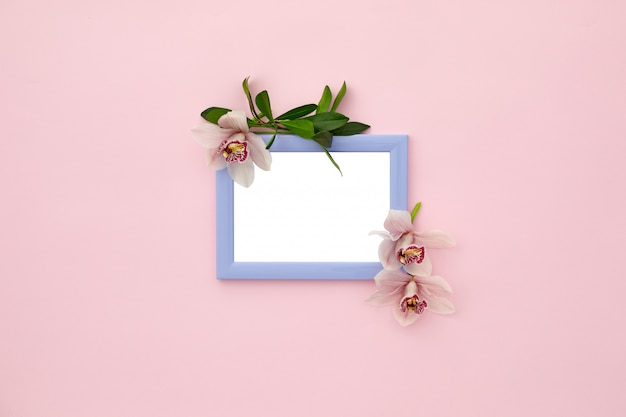 Photo frame decorated with green leaves and orchid flowers