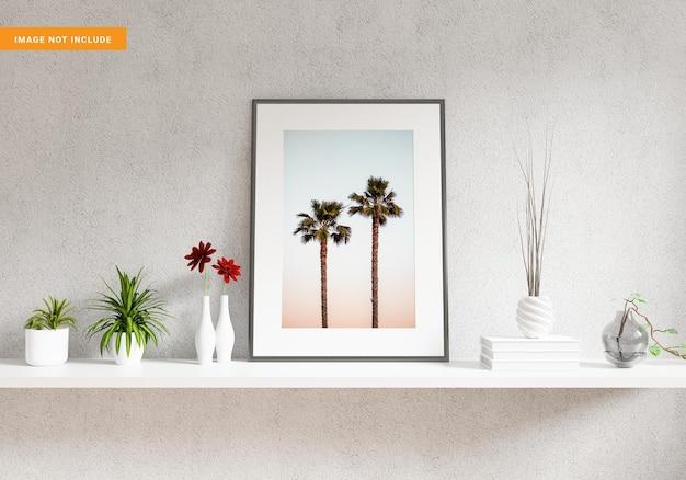 植物や装飾品の3dレンダリングで白い棚にフォトフレームのモックアップ