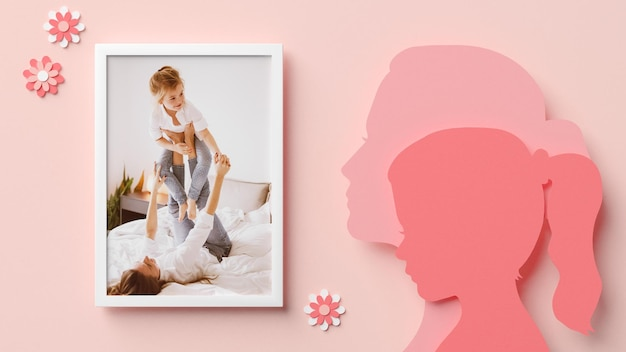 Photo frame mockup with mom and daughter silhouettes in papercut style for mother's day