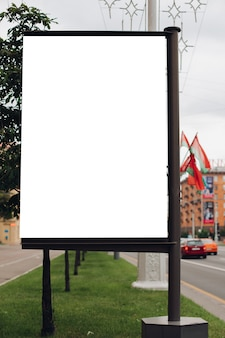Photo of a large billboard that stands on the street, where many people walk