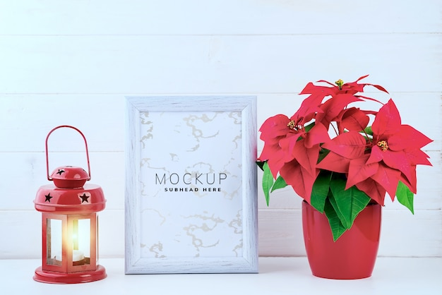 Photo mock up with white frame, poinsettia in a flowerpot and red lantern on white wooden background