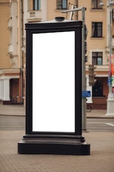 많은 사람들이 걷는 거리에 서있는 큰 광고판의 사진