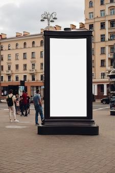 Фотография большого рекламного щита, который стоит на улице, по которой гуляют многие