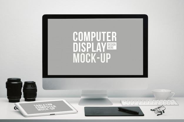 Photographer workspace with blank screen computer display and tablet for mockup on work desk with keyboard, camera lens, eyeglasses, coffee cup and pen tablet