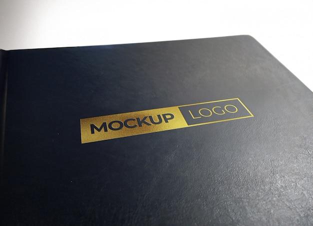 黒い質感のレザーに写実的なゴールドロゴモックアップ