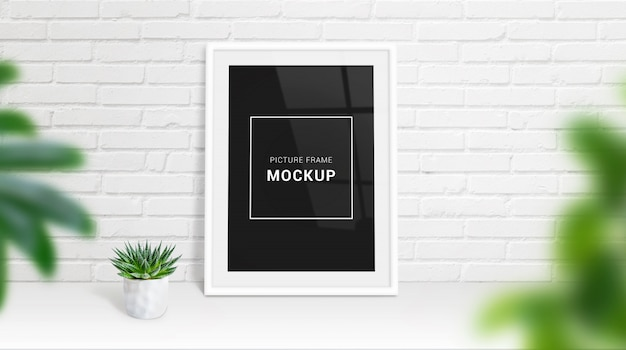 Picture frame mockup leaned on white brick wall. plant beside. art mockup presentation