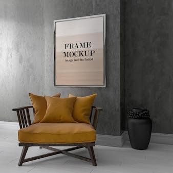 안락 의자 뒤에 회색 벽에 액자 모형