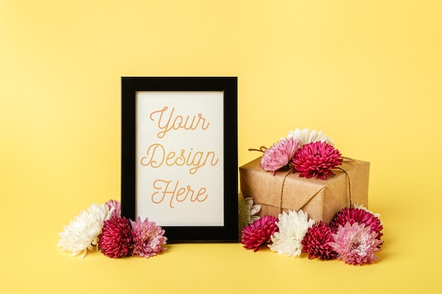 Picture frame mockup with eco zero waste wrapping style gift box and flowers
