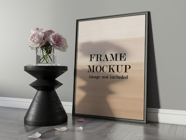 Picture frame on parquet floor beside flowers