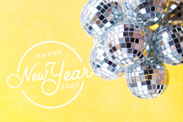 Pile of silver christmas balls on yellow new year background