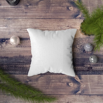 Pillow on a wooden table surrounded by baubles, pines and fir