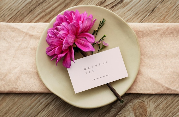 Pink dahlia flower on a beige plate with a card mockup